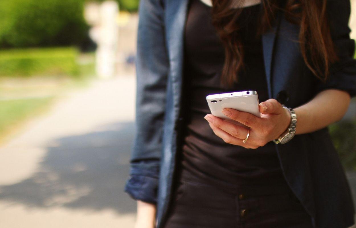 Imagem mostra mulher com celular na mão - frases para bio do Instagram