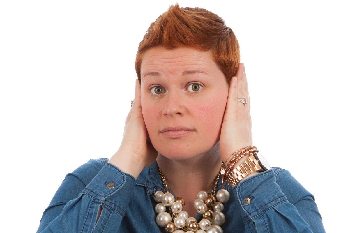 Imagem mostra mulher com mãos nas orelhas - orelha esquerda quente