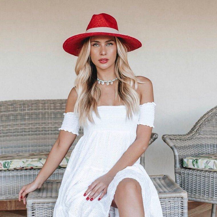 Imagem mostra look com chapéu vermelho - como carregar chapéu na mala