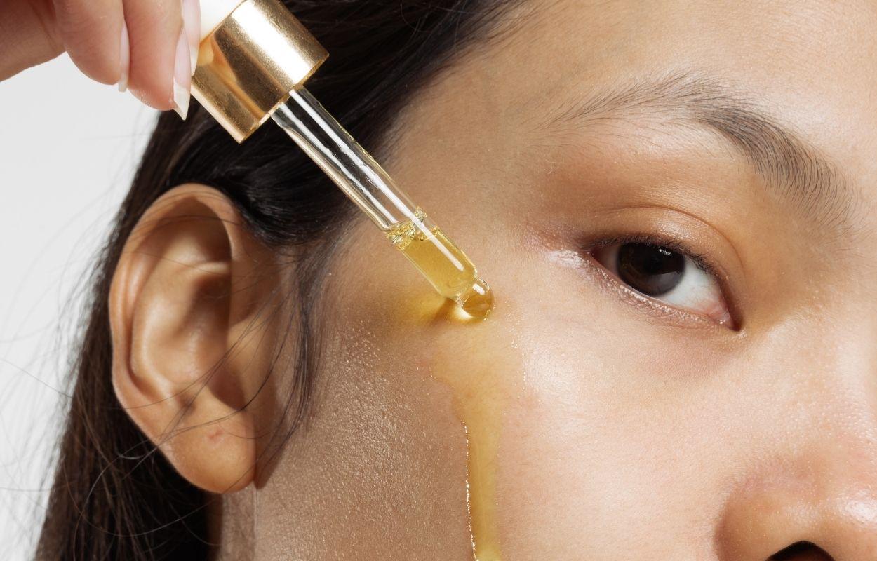 Imagem mostra mulher aplicando óleo no rosto - cleansing oil